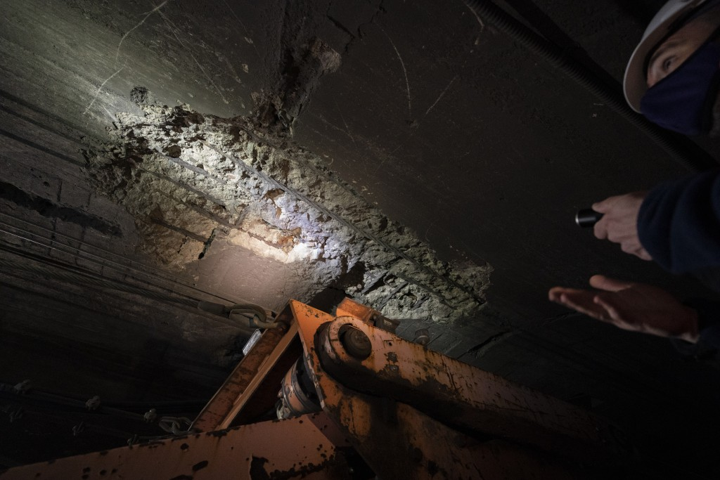 A disintegrating ceiling is illuminated by Amtrak workers as they perform tunnel repairs to a partially flooded train track bed, Saturday, March 20, 2...