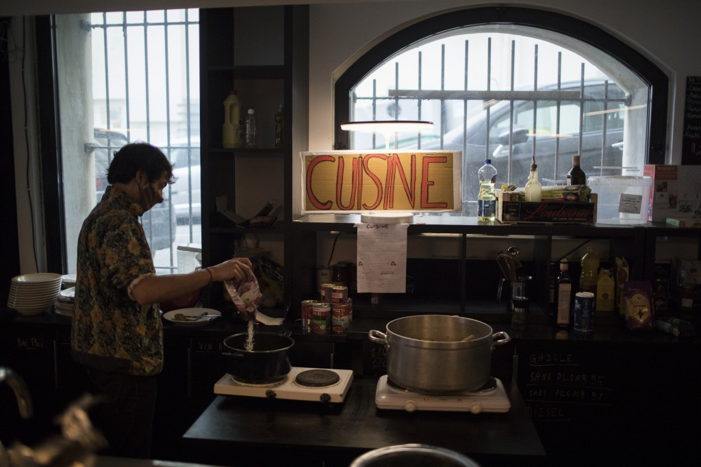 A culture worker cooks food in a makeshift kitchen at the occupied Theatre de La Criee in Marseille, southern France, Friday, March 26, 2021. Out-of-w...