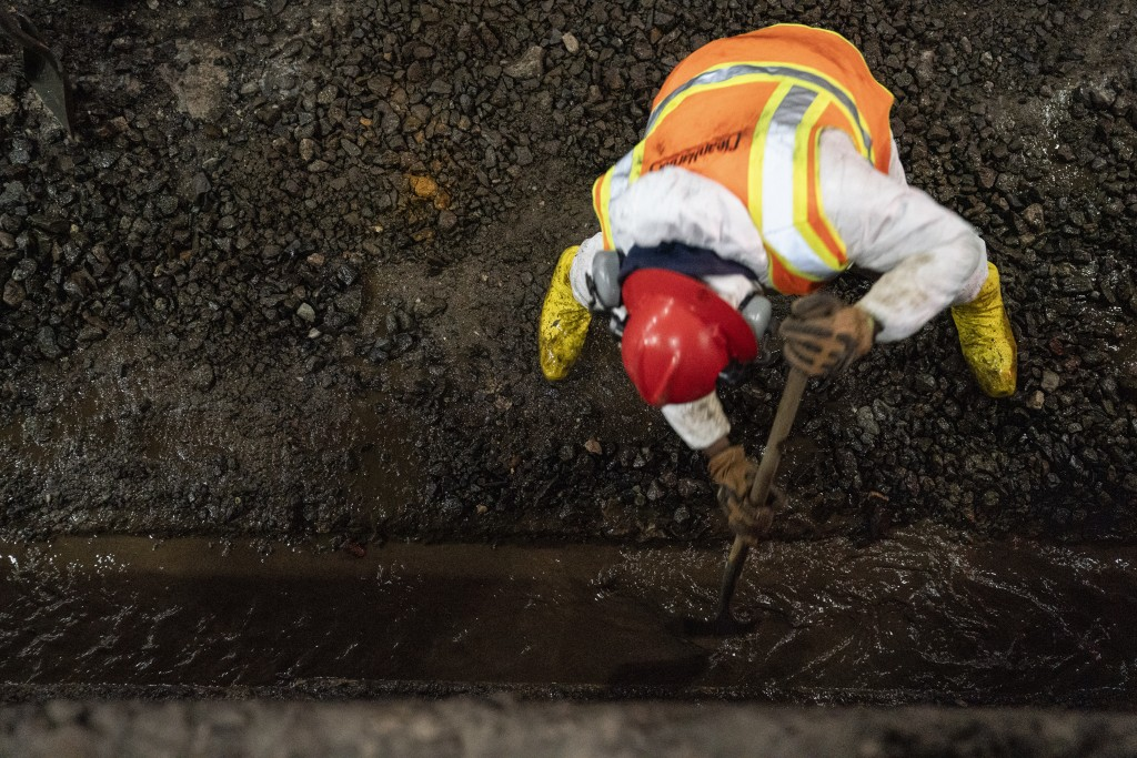 Amtrak workers perform tunnel repairs to a partially flooded train track bed, Saturday, March 20, 2021, in Weehawken, N.J. With a new rail tunnel into...