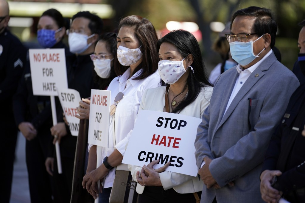FILE - In this Monday, March 22, 2021 file photo, Demonstrators holds signs during a press conference calling to a halt on violence against Asian Amer...