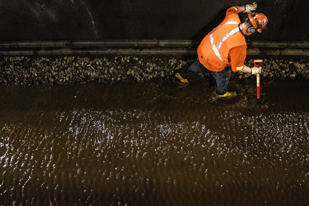Amtrak workers perform tunnel repairs to a partially flooded train track bed, Saturday, March 20, 2021, in Weehawken, N.J.  With a new rail tunnel int...