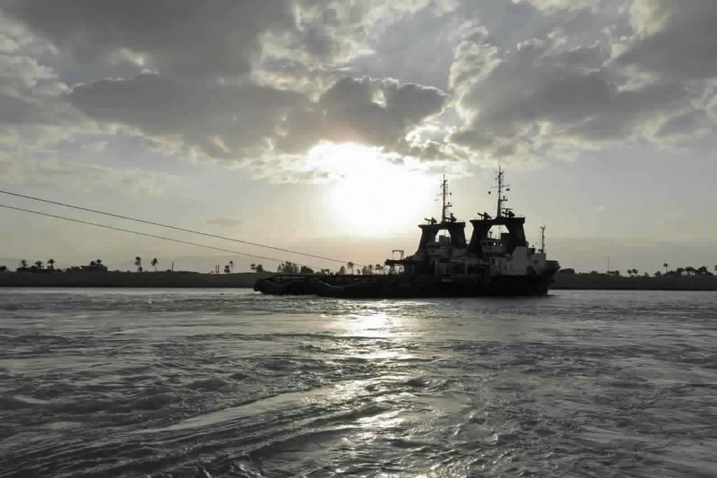 In this photo released by the Suez Canal Authority, tug boats approach the Panama-flagged, Japanese-owned Ever Given, which is lodged across the Suez ...