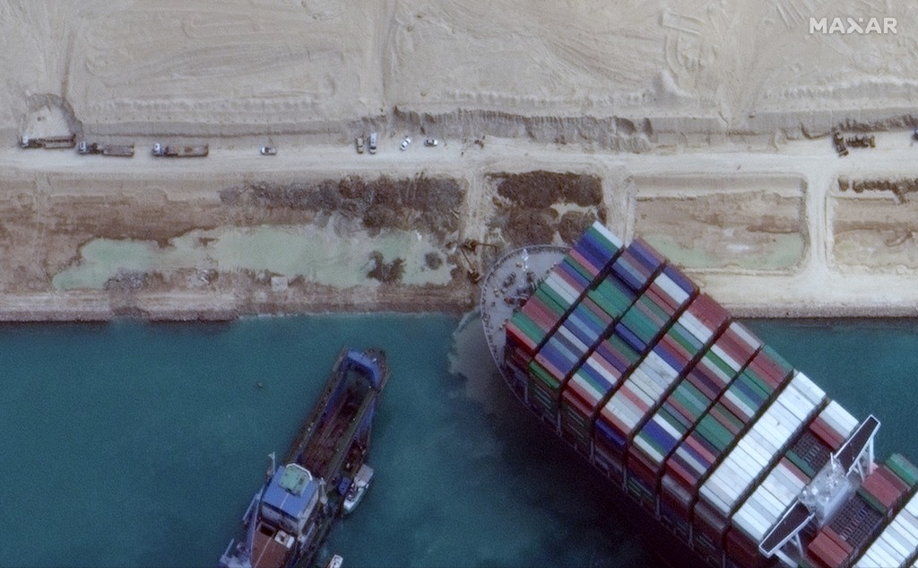 This satellite image from Maxar Technologies shows excavation work in an atempt to free the cargo ship MV Ever Given that is stuck in the Suez Canal n...