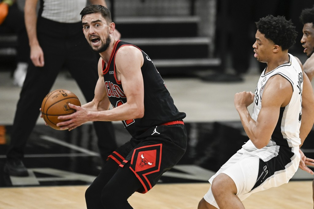 Chicago Bulls' Tomas Satoransky, left, looks to pass as he is defended by San Antonio Spurs' Keldon Johnson during the second half of an NBA basketbal...