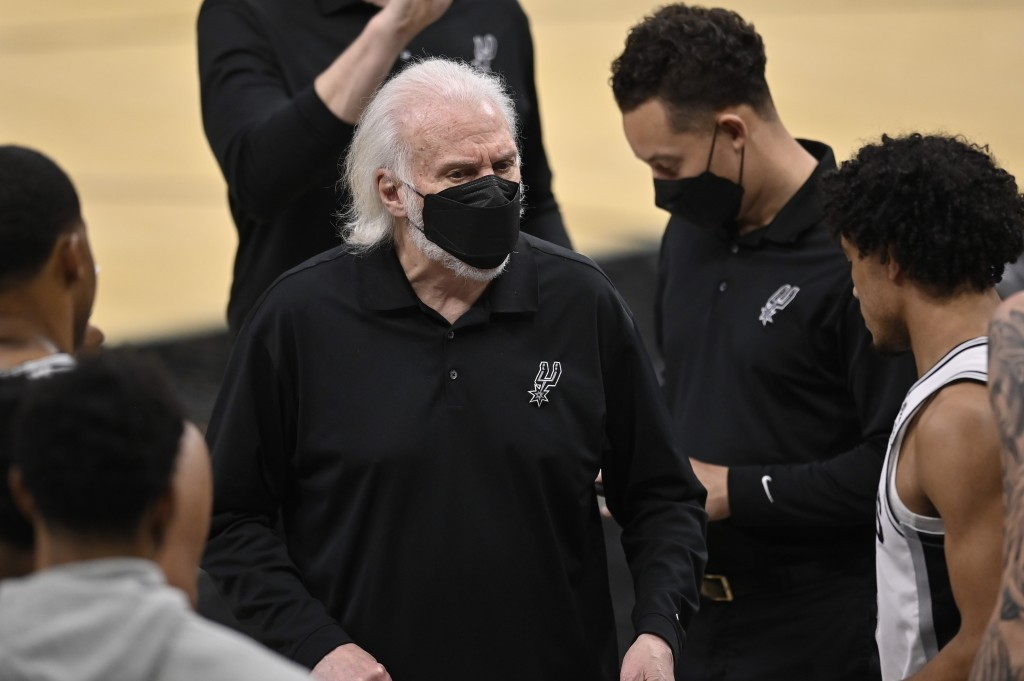 San Antonio Spurs head coach Gregg Popovich, center, talks to his players during a timeout in the second half of an NBA basketball game against the Ch...