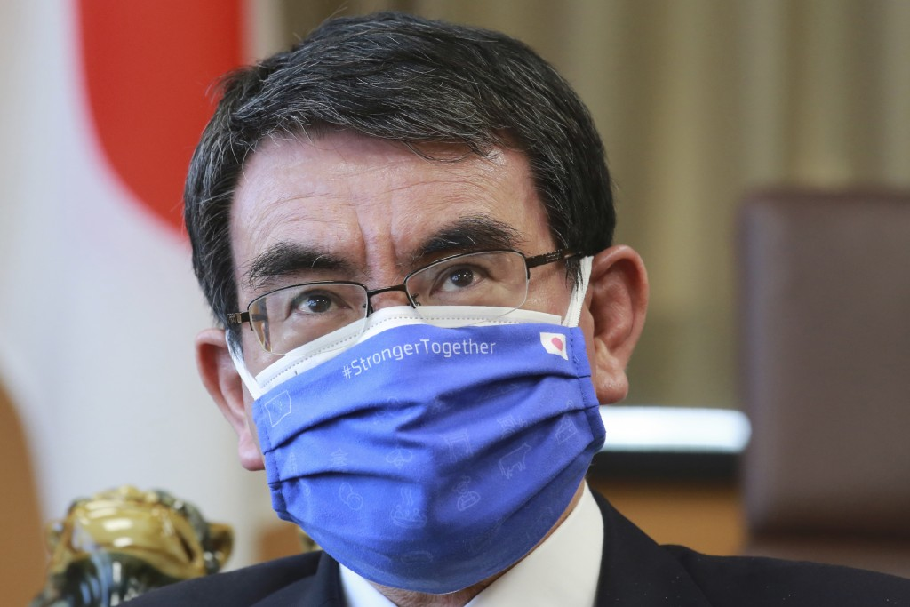 Japanese Vaccine Minister Taro Kono wearing a face mask with Japanese and EU flags on it speaks during an interview in Tokyo, Monday, March 29, 2021. ...