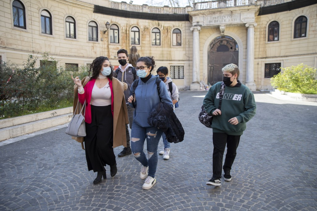 Matteo Coccimiglio, right, leaves the Ripetta art school in Rome, Wednesday, March 24, 2021. Matteo is an 18-year-old student who identifies as a man ...