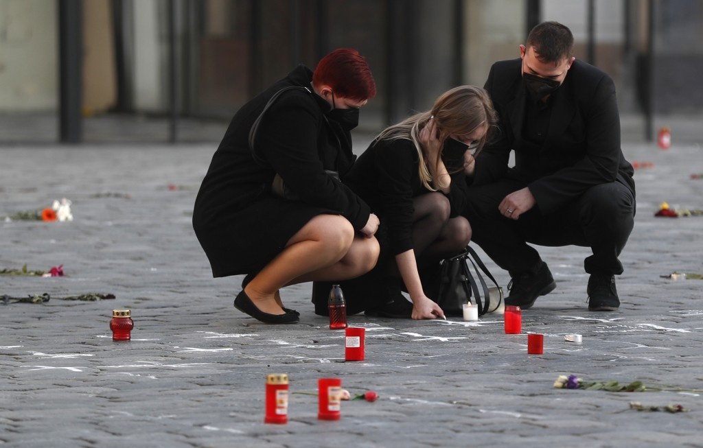 People pay respect to victims of the COVID-19 pandemic at a spontaneous memorial place set at the Old Town Square in Prague, Czech Republic, Monday, M...