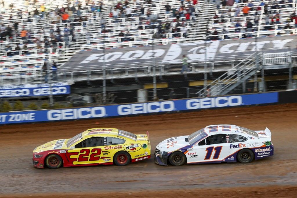 Driver Joey Logano (22) leads Denny Hamlin (11) through Turn 4 during an NASCAR Cup Series auto race, Monday, March 29, 2021, in Bristol, Tenn. (AP Ph...