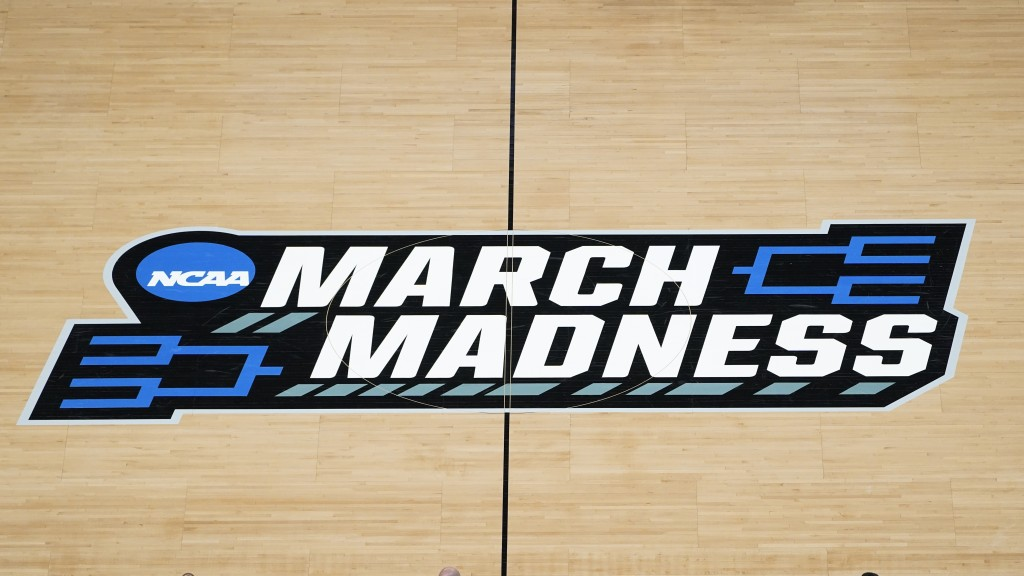 FILE - In this March 20, 2021, file photo the March Madness logo is shown on the court during the first half of a men's college basketball game in the...