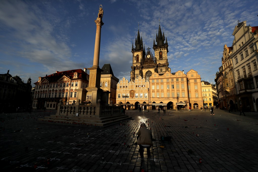 A man pays respect to victims of the COVID-19 pandemic at a spontaneous memorial place set at the Old Town Square in Prague, Czech Republic, Monday, M...