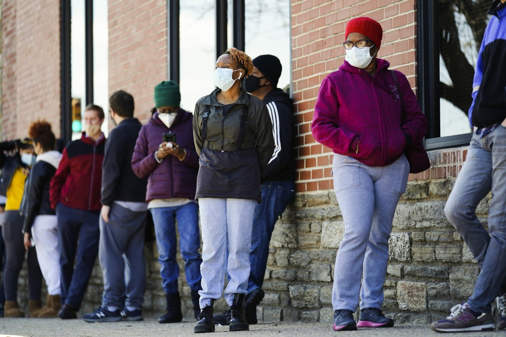 People wearing face masks as a precaution against the coronavirus wait in line to receive COVID-19 vaccines at a site in Philadelphia, Monday, March 2...