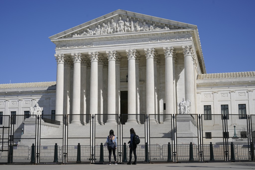 FILE - In this March 21, 2021, file photo people view the Supreme Court building from behind security fencing on Capitol Hill in Washington after port...