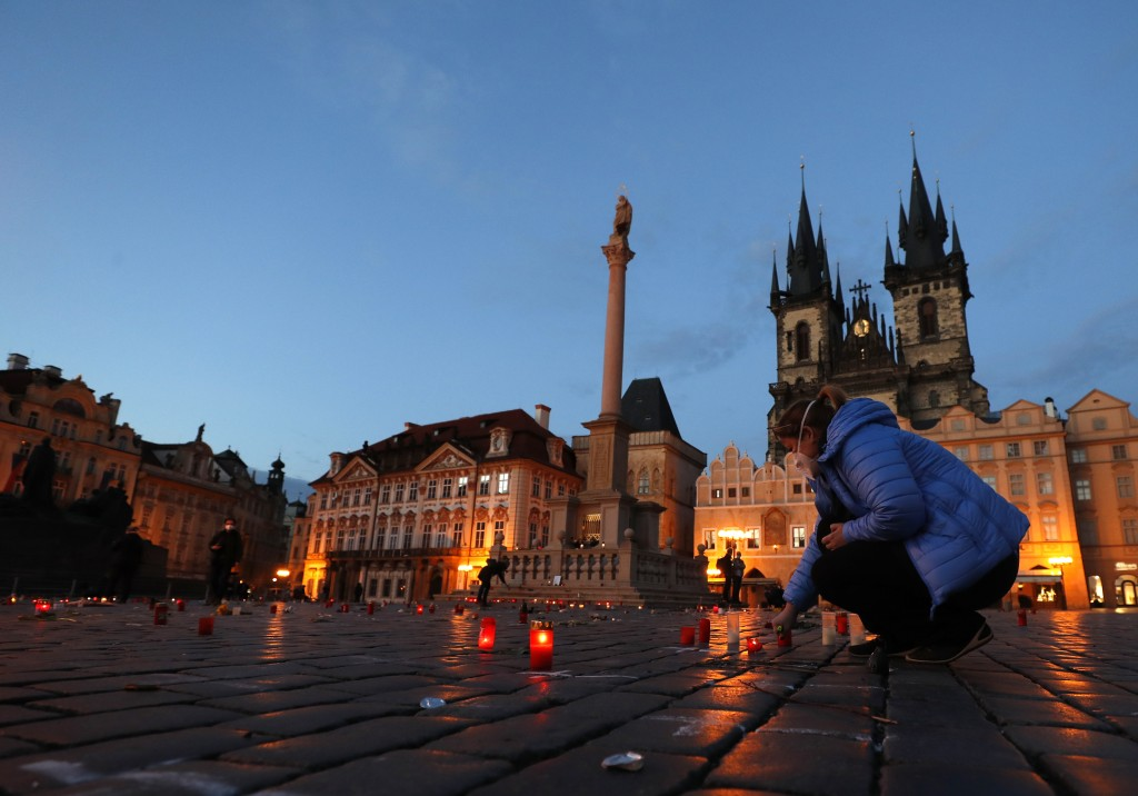 A woman lights up a candle to pay respect to victims of the COVID-19 pandemic at a spontaneous memorial place set at the Old Town Square in Prague, Cz...