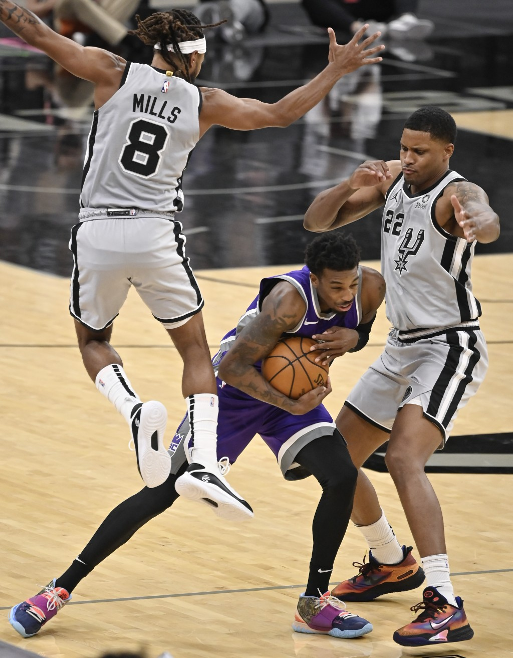 Sacramento Kings' Delon Wright, center, tangles with San Antonio Spurs' Patty Mills (8) and Rudy Gay during the second half of an NBA basketball game ...