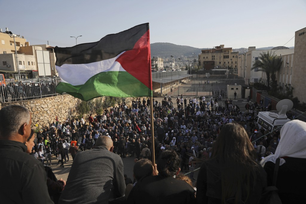 A Palestinian flag flies over the annual Land Day rally in the Arab city of Arraba, northern Israel, Tuesday, March 30, 2021. Land Day rallies by Pale...