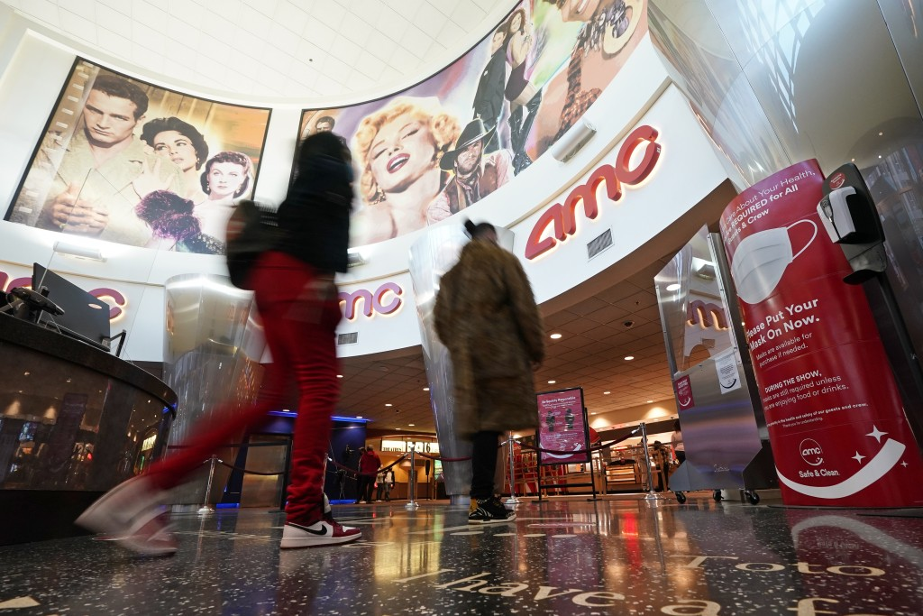 FILE - In this March 15, 2021, file photo movie patrons arrive to see a film at the AMC 16 theater in Burbank, Calif. Los Angeles County can reopen ev...