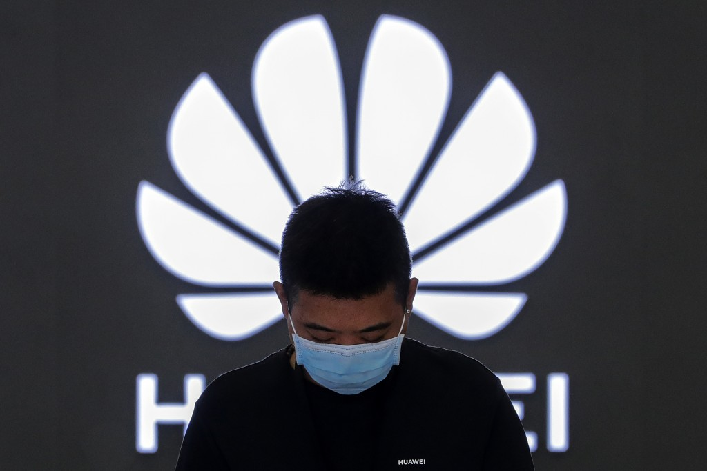 FILE - In this Aug. 31, 2020, file photo, an employee wearing a face mask to help curb the spread of the coronavirus stands inside a Huawei flagship s...