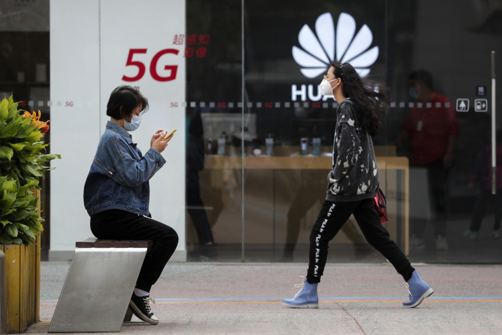 FILE - In this Oct. 11, 2020, file photo, a woman wearing a face mask to help curb the spread of the coronavirus browses her smartphone as a masked wo...