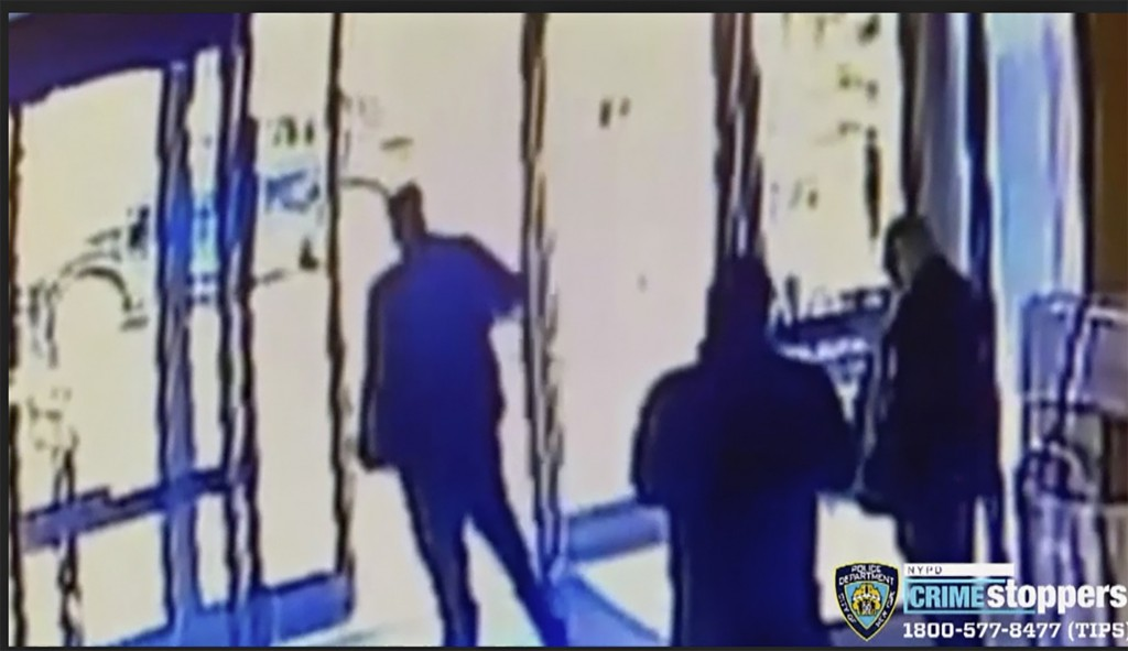 This image taken from surveillance video provided by the New York City Police Department shows an apartment building employee, center, closing the bui...