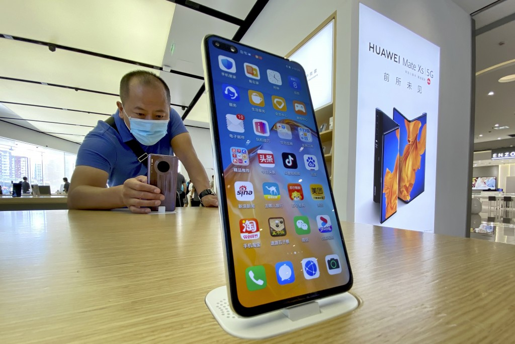 A shopper tries out the smartphones at a Huawei store in Beijing on Sept. 8, 2020.  Chinese tech giant Huawei said Wednesday, March 31, 2021, it eked ...