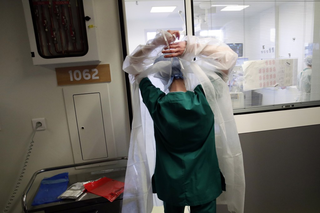 A medical worker prepares to tend to a patient affected with the COVID-19 in the Amiens Picardie hospital Tuesday, March 30, 2021 in Amiens, 160 km (1...