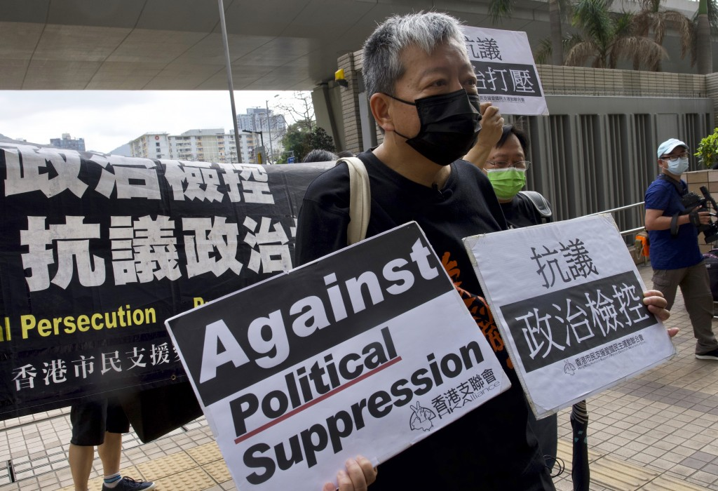 Pro-democracy activist Lee Cheuk-yan, center, holds placards as he arrives at a court in Hong Kong Thursday, April 1, 2021. Seven pro-democracy advoca...