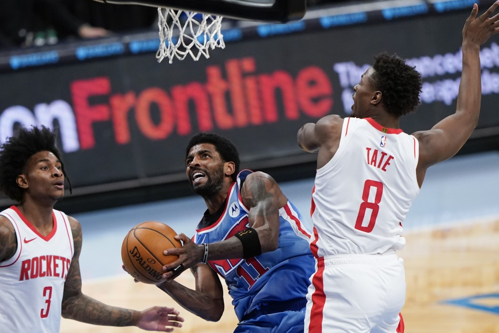 Houston Rockets' Kevin Porter Jr. (3) and Jae'Sean Tate (8) defend against Brooklyn Nets' Kyrie Irving during the first half of an NBA basketball game...