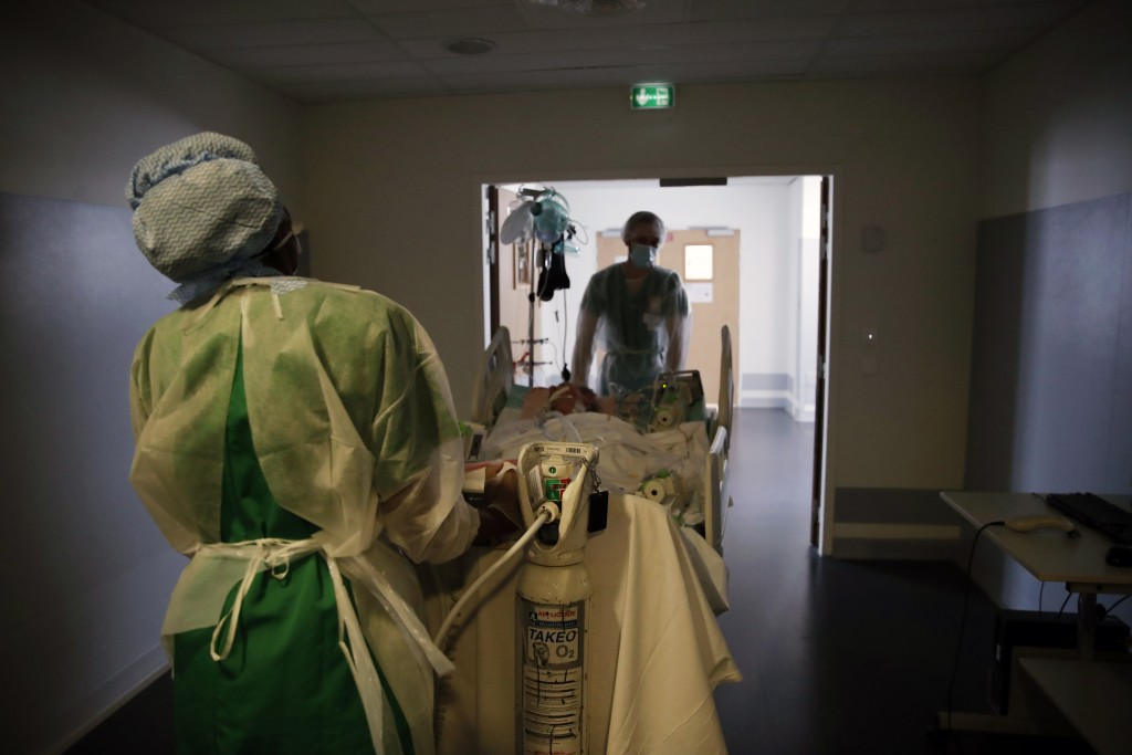 Medical workers move a patient affected with the COVID-19 for a checking scanner in the Amiens Picardie hospital Tuesday, March 30, 2021 in Amiens, 16...