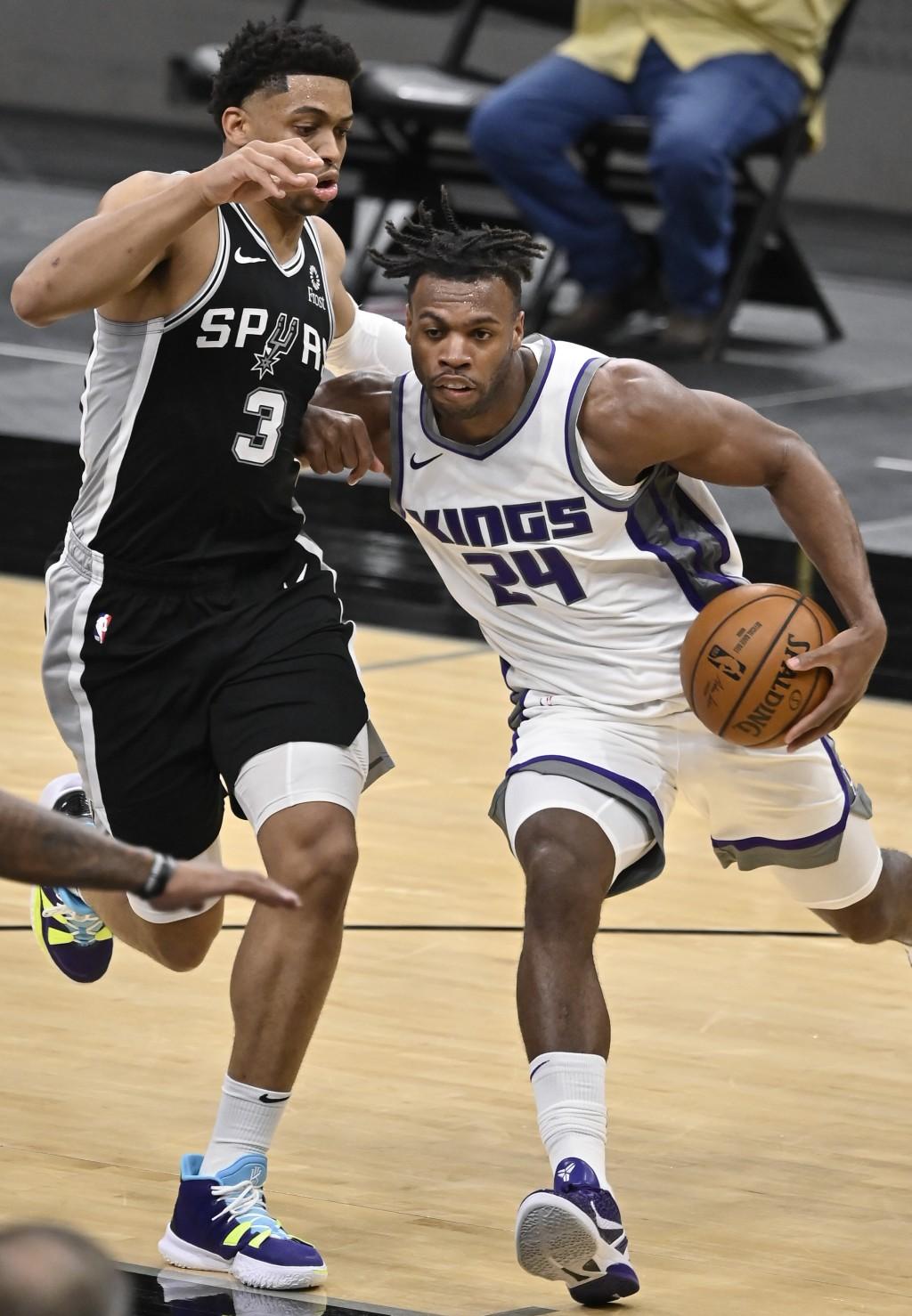 Sacramento Kings' Buddy Hield (24) drives against San Antonio Spurs' Keldon Johnson during the second half of an NBA basketball game Wednesday, March ...