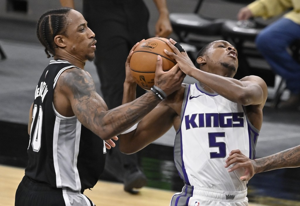 San Antonio Spurs' DeMar DeRozan, left, strips the ball from Sacramento Kings' De'Aaron Fox during the second half of an NBA basketball game Wednesday...