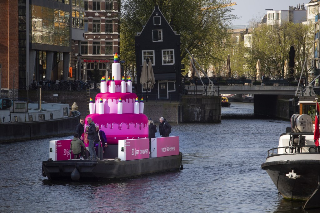 A huge inflatable pink cake with candles spouting rainbow flames glided through the Amsterdam canals Thursday as the Dutch capital celebrated the 20th...
