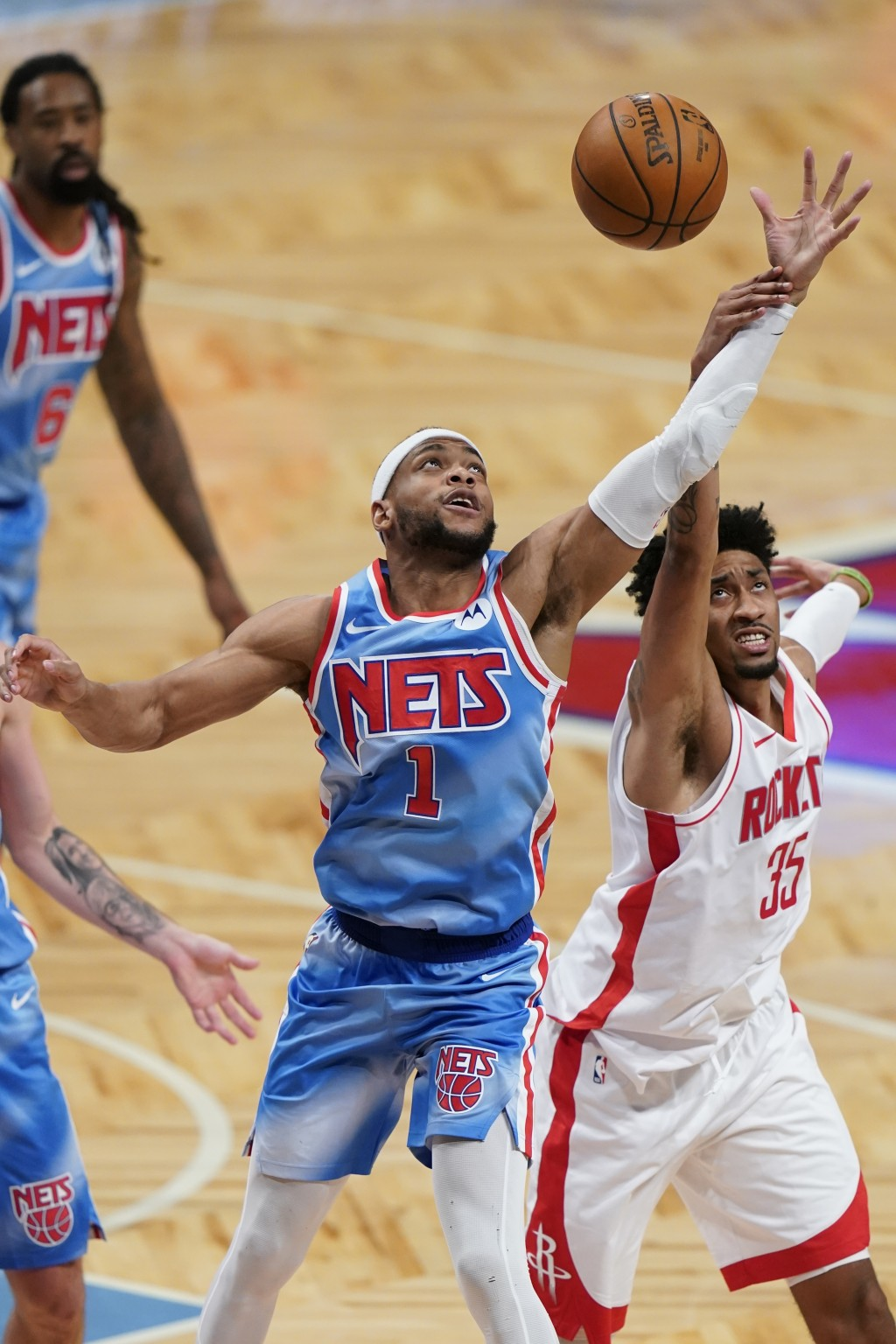 Houston Rockets' Christian Wood (35) and Brooklyn Nets' Bruce Brown (1) reach for the ball during the second half of an NBA basketball game Wednesday,...