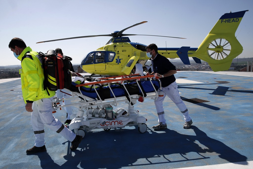 Medical workers bring an emergency arrival on the rooftop of the Amiens Picardie hospital Tuesday, March 30, 2021 in Amiens, 160 km (100 miles) north ...