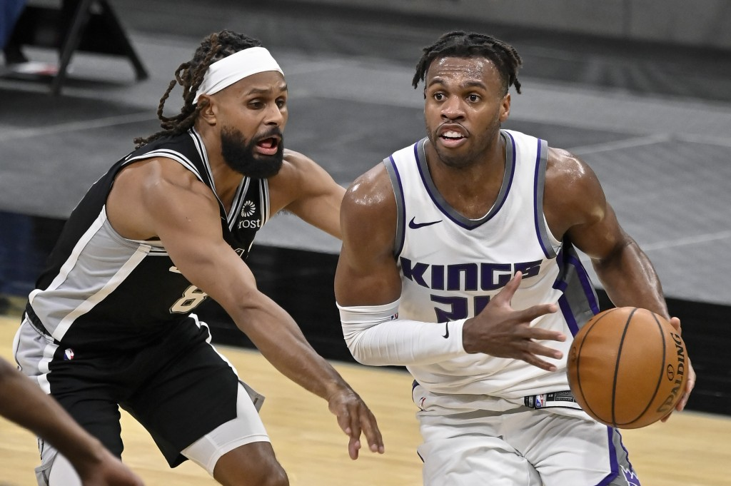 Sacramento Kings' Buddy Hield, right, drives around San Antonio Spurs' Patty Mills during the second half of an NBA basketball game, Wednesday, March ...