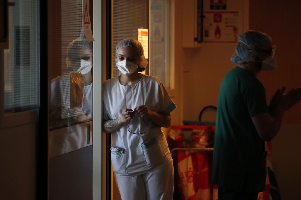 Medical workers wait to tend to a patient affected with the COVID-19 in the Amiens Picardie hospital Tuesday, March 30, 2021 in Amiens, 160 km (100 mi...