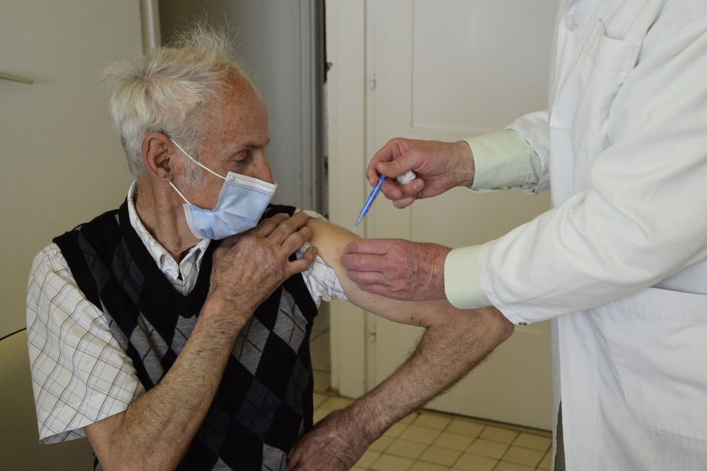 General practitioner Gyorgy Teleki vaccinates a patient with the second dose of COVID-19 vaccine produced by Chinese Sinopharm in Taplanszentkereszt, ...