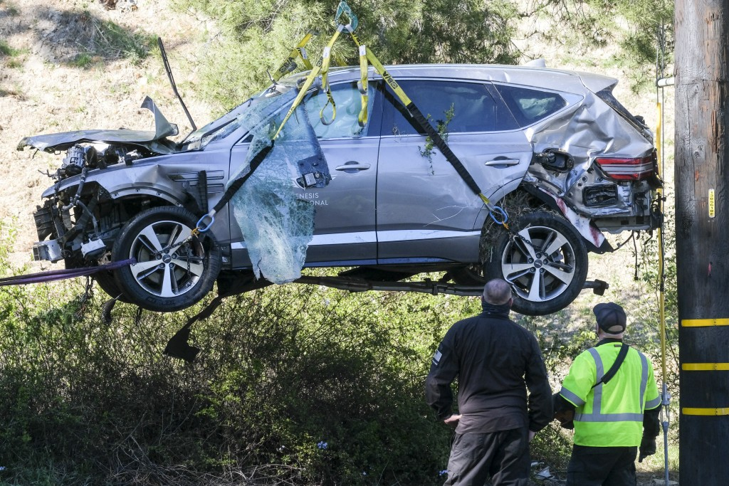 FILE - In this Feb. 23, 2021, file photo a crane is used to lift a vehicle following a rollover accident involving golfer Tiger Woods, in the Rancho P...
