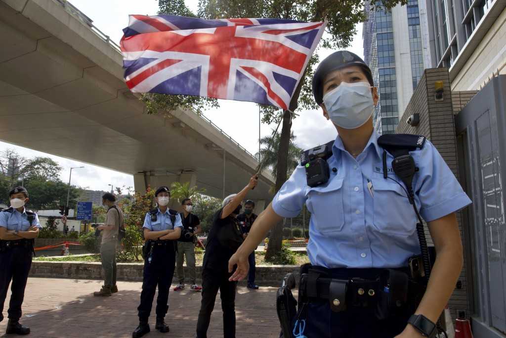 A pro-democracy supporter waves a British flag as police officers stand guard outside a court in Hong Kong Thursday, April 1, 2021. Seven pro-democrac...