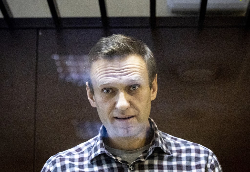 In this photo taken on Saturday, Feb. 20, 2021, Russian opposition leader Alexei Navalny looks at photographers standing behind a glass of the cage in...