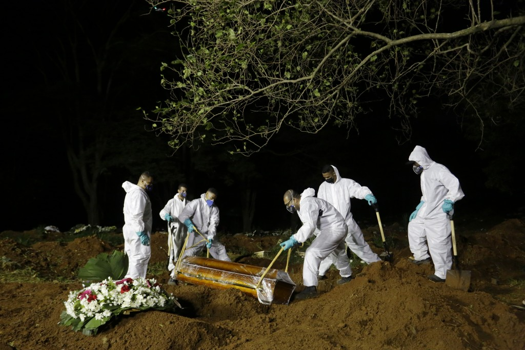 Cemetery workers lower the coffin of a COVID-19 victim into his grave at the Vila Formosa cemetery in Sao Paulo, Brazil, late Wednesday, March 31, 202...