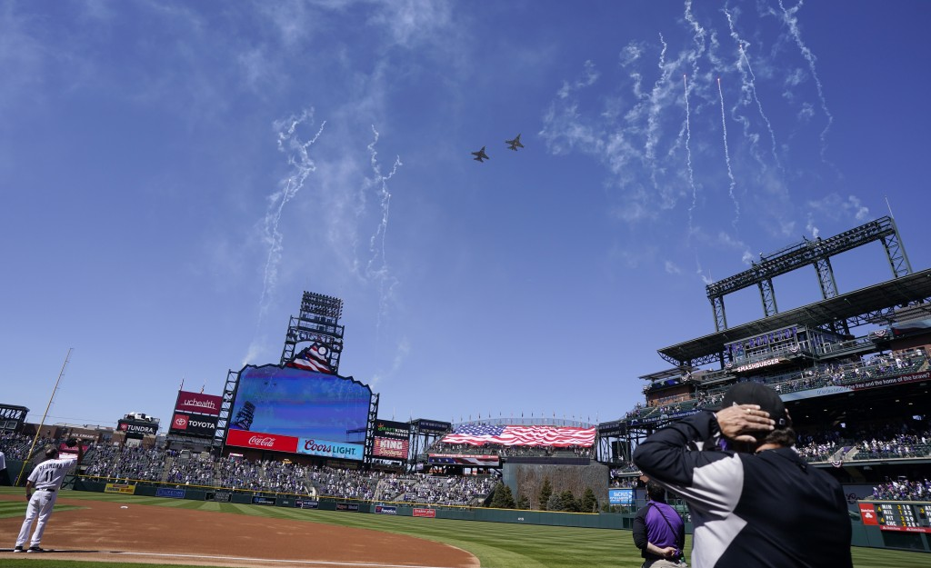 Two F-16  jets from Buckley Air Force Base in Aurora, Colo., fly over Coors Field before a baseball game between the Los Angeles Dodgers and the Color...