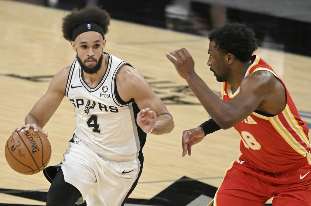 San Antonio Spurs' Derrick White (4) drives against Atlanta Hawks' Solomon Hill during the first half of an NBA basketball game Thursday, April 1, 202...