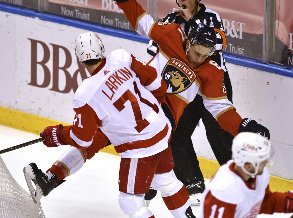 Detroit Red Wings center Dylan Larkin (71) gets called for roughing after colliding with Florida Panthers defenseman Riley Stillman (61) during the se...
