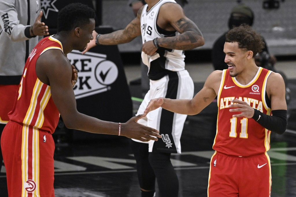 Atlanta Hawks' Trae Young (11) and Clint Capela celebrate the team's double-overtime victory against the San Antonio Spurs in an NBA basketball game T...