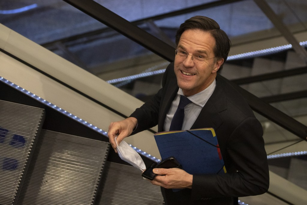 Caretaker Dutch Prime Minister Mark Rutte leaves after surviving a no-confidence motion in parliament in The Hague, Netherlands, early Friday, April 2...