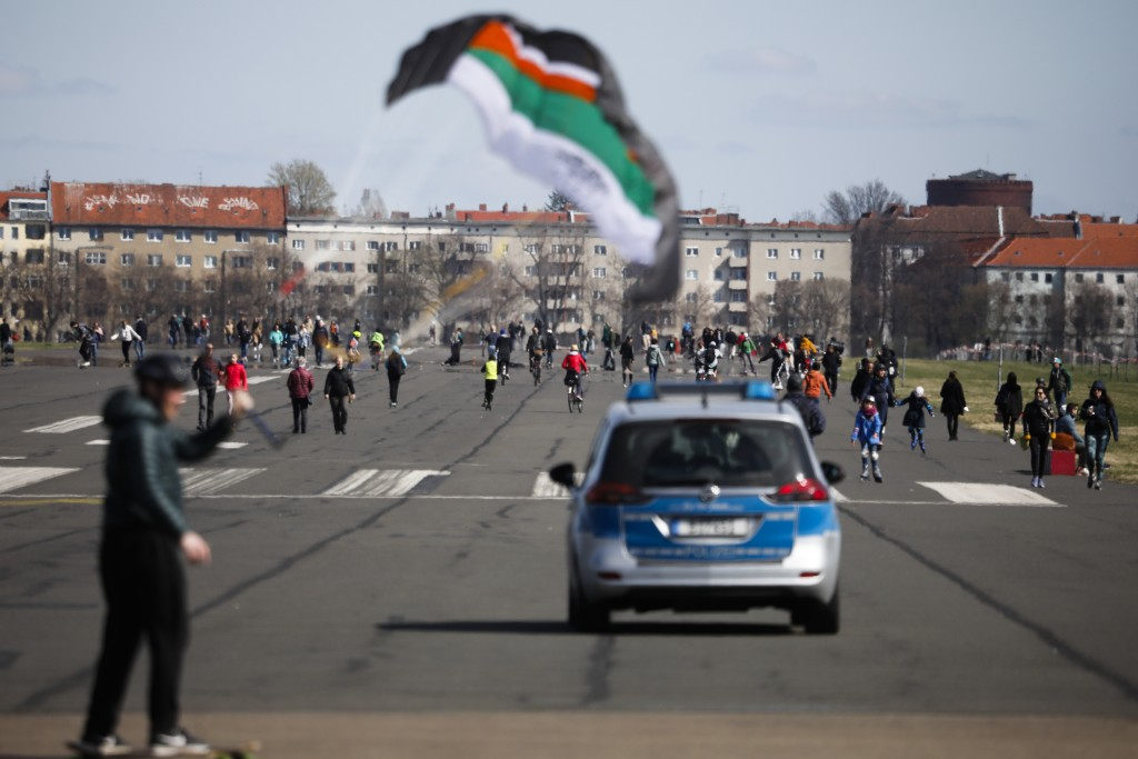 A police car patrols people walking on the runway of the former Tempelhof airport, that is now a public park, in Berlin, Germany, Friday, April 2, 202...