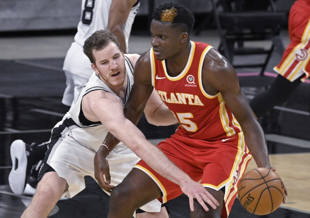 Atlanta Hawks' Clint Capela, right, drives against San Antonio Spurs' Jakob Poeltl during the first half of an NBA basketball game Thursday, April 1, ...