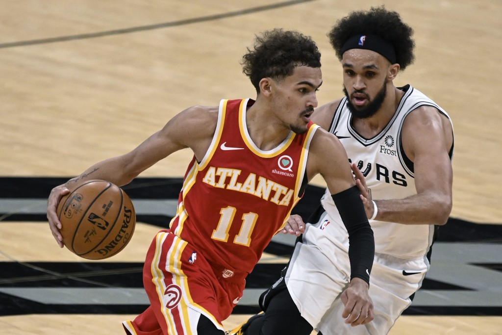 Atlanta Hawks' Trae Young (11) drives against San Antonio Spurs' Derrick White during the second half of an NBA basketball game Thursday, April 1, 202...