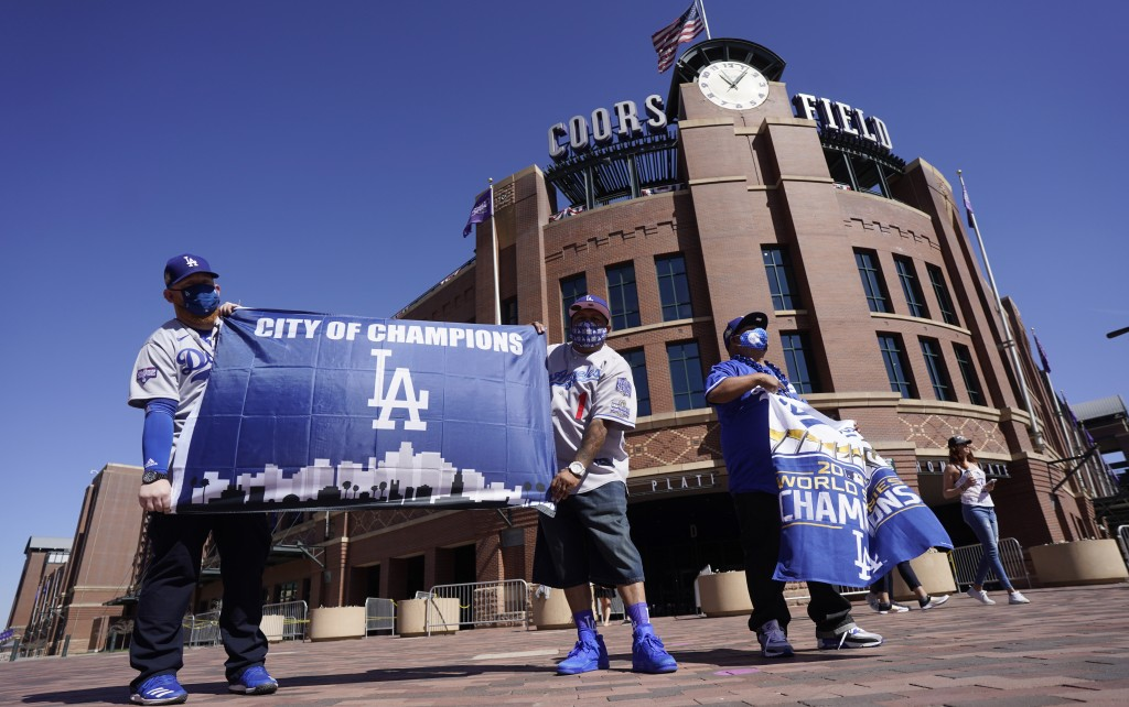 Los Angeles Dodgers fans Oliver Olson, left, of San Diego, Juan Campo and Rudy Soto, both of Los Angeles, hold up flags outside the main entrance to C...
